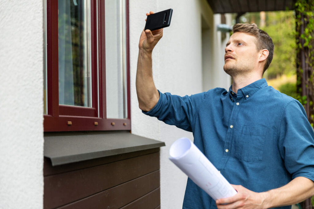 Houston property manager taking a photo of a window outside rental home
